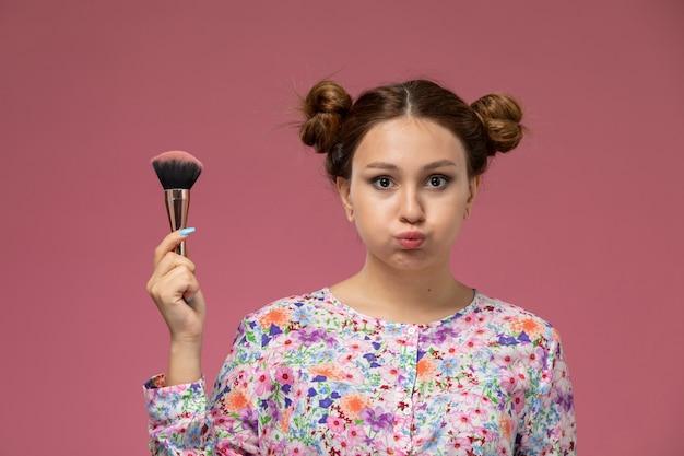 Vooraanzicht jonge vrouw in bloem ontworpen shirt met een make-up borstel op de roze achtergrond