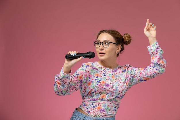 Vooraanzicht jonge vrouw in bloem ontworpen shirt met een microfoon zingen op de roze achtergrond