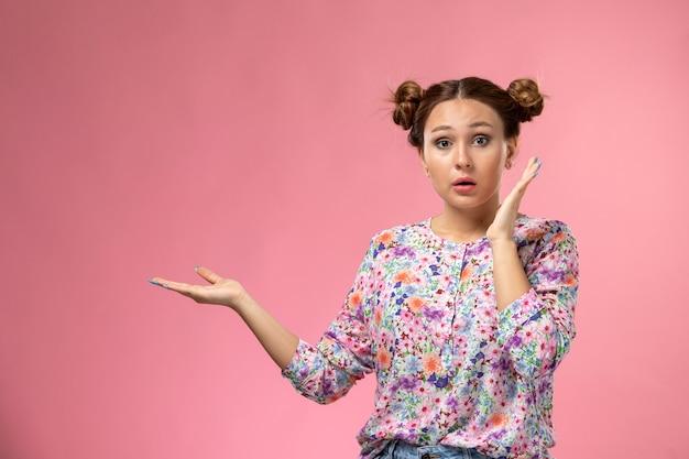 Vooraanzicht jonge vrouw in bloem ontworpen shirt poseren met verbaasde uitdrukking op het roze bureau