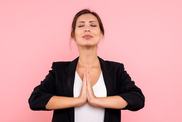 Vooraanzicht jonge vrouw in donker jasje bidden op roze achtergrond