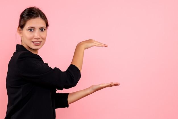 Vooraanzicht jonge vrouw in donker jasje imiteren dat ze iets op roze achtergrond houdt