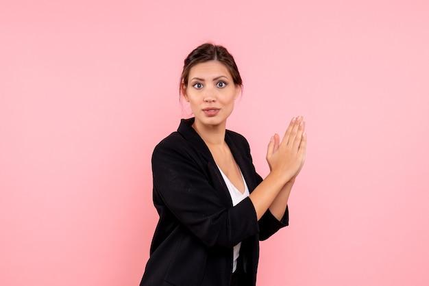 Vooraanzicht jonge vrouw in donker jasje klappen op roze achtergrond