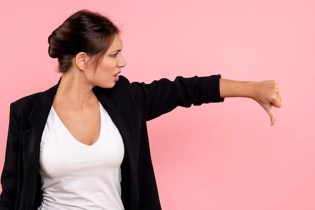 Vooraanzicht jonge vrouw in donker jasje ontevreden op roze achtergrond