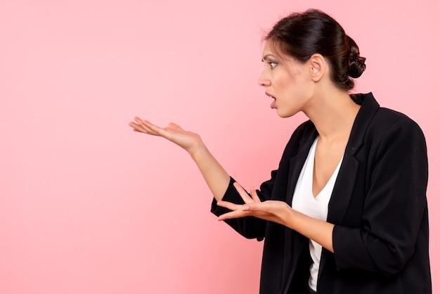 Vooraanzicht jonge vrouw in donker jasje ruzie met iemand op roze achtergrond