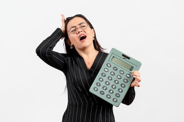 Vooraanzicht jonge vrouw in donker strikt pak met grote rekenmachine op lichte witte achtergrond schoonheid zakelijke kantoorbaan mode