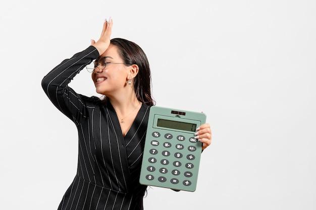 Vooraanzicht jonge vrouw in donker strikt pak met grote rekenmachine op witte achtergrond baan schoonheid vrouw mode zakelijke kantoor