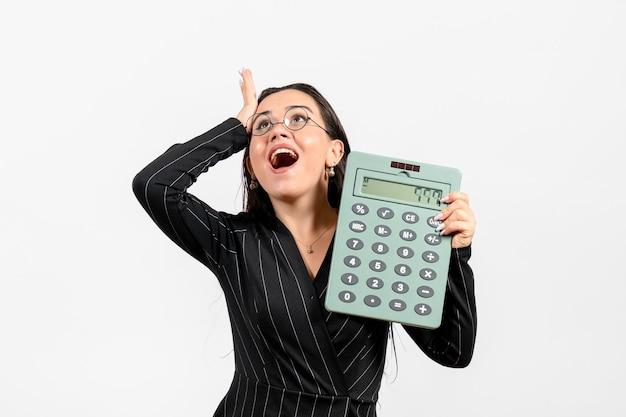 Vooraanzicht jonge vrouw in donker strikt pak met rekenmachine op licht-witte achtergrond baan vrouw kantoor mode zakelijke schoonheid