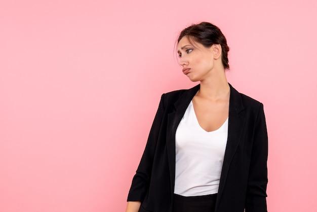 Vooraanzicht jonge vrouw in donkere jas benadrukt op roze achtergrond