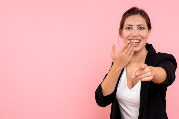 Vooraanzicht jonge vrouw in donkere jas en wit overhemd lachen op roze achtergrond