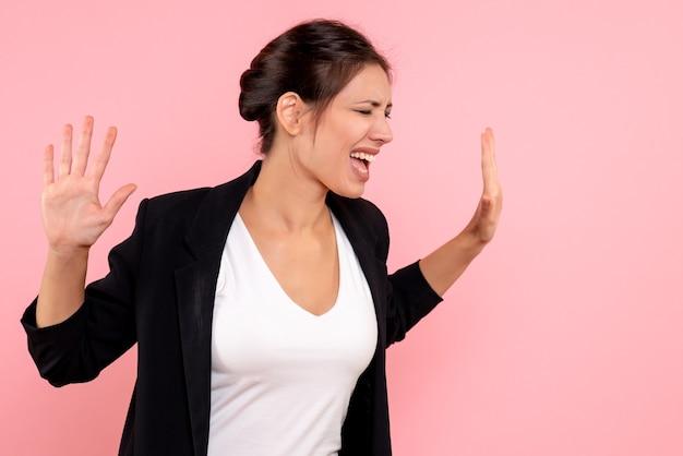 Vooraanzicht jonge vrouw in donkere jas en wit overhemd schreeuwen op roze achtergrond