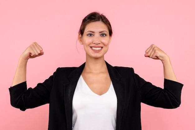 Vooraanzicht jonge vrouw in donkere jas glimlachend en buigen op roze achtergrond