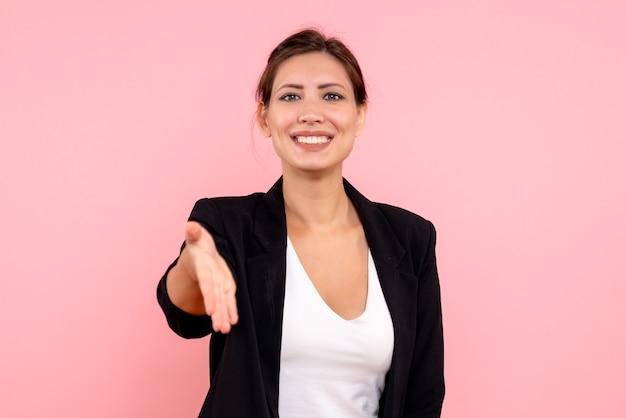 Vooraanzicht jonge vrouw in donkere jas groet op een roze achtergrond