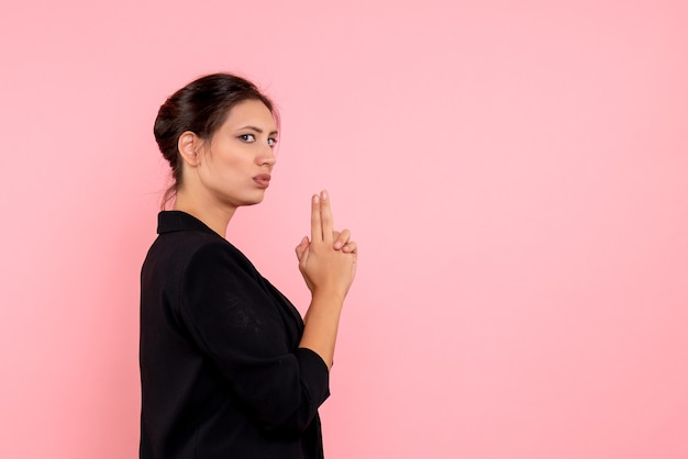Vooraanzicht jonge vrouw in donkere jas in pistool houden pose op roze achtergrond