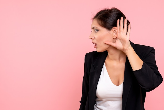Vooraanzicht jonge vrouw in donkere jas luisteren op de roze achtergrond