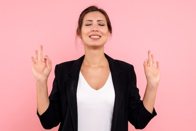 Vooraanzicht jonge vrouw in donkere jas mediteren op roze achtergrond
