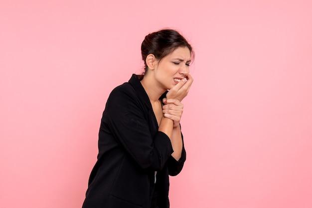 Vooraanzicht jonge vrouw in donkere jas met kiespijn op roze achtergrond