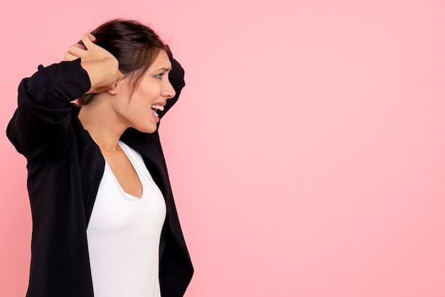 Vooraanzicht jonge vrouw in donkere jas nerveus op roze achtergrond