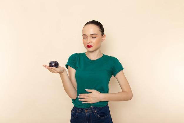 Vooraanzicht jonge vrouw in donkergroen shirt en spijkerbroek met buikpijn als gevolg van blauwe pruim op beige