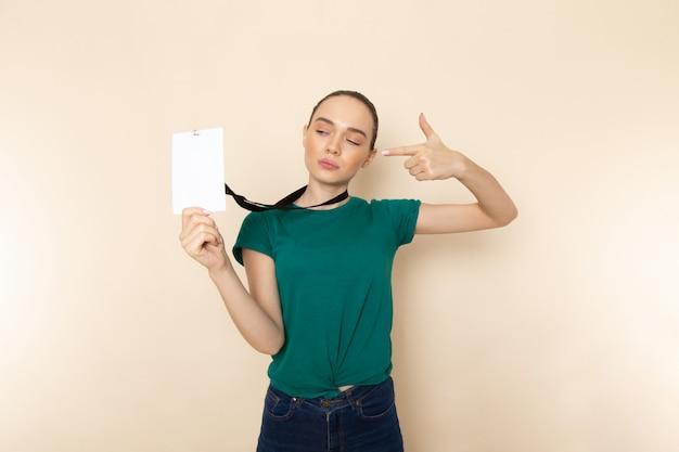 Vooraanzicht jonge vrouw in donkergroen shirt en spijkerbroek met identiteitskaart op beige