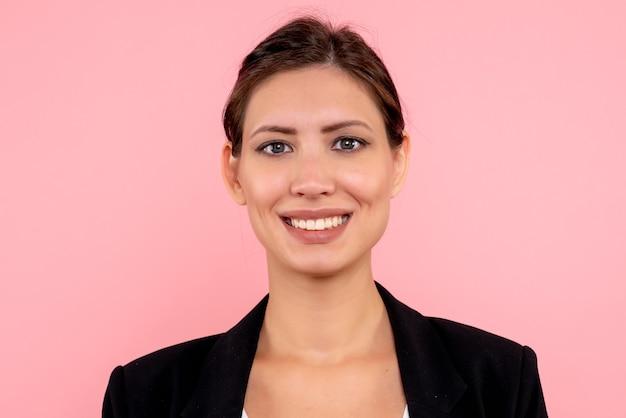 Vooraanzicht jonge vrouw in een donkere jas lachend op roze achtergrond