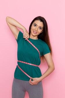 Vooraanzicht jonge vrouw in groen t-shirt haar lichaam meten op de roze muur taille sport oefening training schoonheid slanke atleet