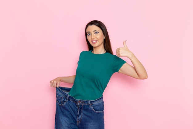 Vooraanzicht jonge vrouw in groen t-shirt haar taille controleren en glimlachend op licht roze muur taille sport oefening trainingen schoonheid slanke atleet vrouw