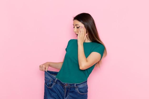 Vooraanzicht jonge vrouw in groen t-shirt haar taille controleren op de lichtroze muur taille sport oefening trainingen schoonheid slanke atleet vrouw