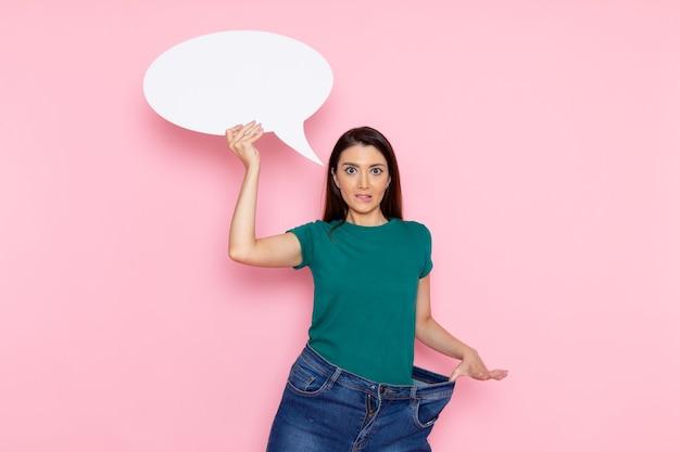 Vooraanzicht jonge vrouw in groen t-shirt met groot wit bord op de roze muur taille sport oefening training schoonheid slanke atleet