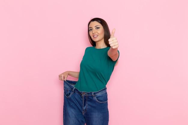 Vooraanzicht jonge vrouw in groen t-shirt wat betreft haar spijkerbroek op roze muur taille sport oefening trainingen schoonheid slanke atleet