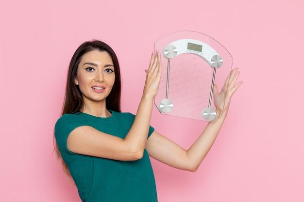 Vooraanzicht jonge vrouw in groene t-shirt met schalen op de roze muur taille oefening training schoonheid slanke vrouwelijke sport