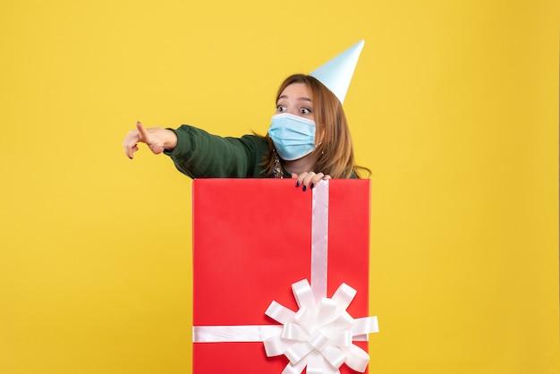 Vooraanzicht jonge vrouw in huidige doos in steriel masker