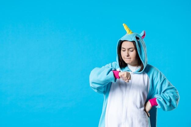 Vooraanzicht jonge vrouw in kigurumi voor pyjama party controle tijd op blauwe achtergrond rust cartoon droom slaap kleur laat plezier nacht anime bed spel