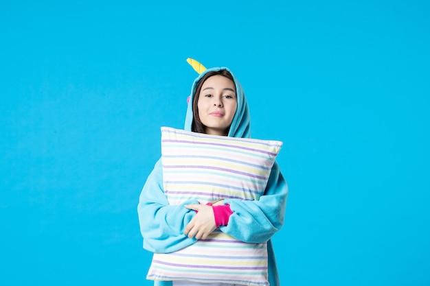 Vooraanzicht jonge vrouw in kigurumi voor pyjama party holding kussen op blauwe achtergrond cartoon droom slaap spel nacht plezier kleur anime laat bed