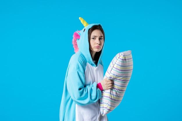 Vooraanzicht jonge vrouw in kigurumi voor pyjama party holding kussen op blauwe achtergrond cartoon droom slaap vrienden spel nacht plezier kleur anime bed