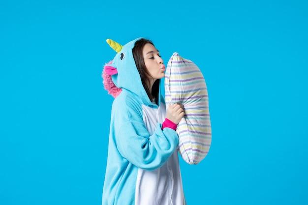 Vooraanzicht jonge vrouw in kigurumi voor pyjama party holding kussen op blauwe achtergrond cartoon droom slaap vrienden spel nacht plezier kleur anime laat bed dier