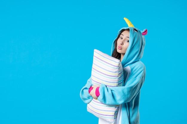 Vooraanzicht jonge vrouw in kigurumi voor pyjama party holding kussen op blauwe achtergrond cartoon droom slaap vrienden spel nacht plezier kleur anime laat bed