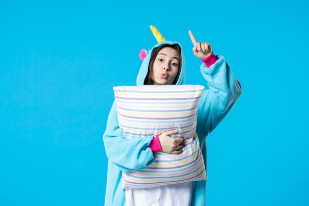 Vooraanzicht jonge vrouw in kigurumi voor pyjama party holding kussen op blauwe achtergrond cartoon game droom slaap vrienden nacht kleur anime laat bed
