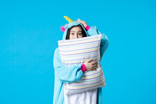 Vooraanzicht jonge vrouw in kigurumi voor pyjama party holding kussen op blauwe achtergrond cartoon spel droom slaap nacht plezier kleur anime laat bed