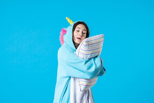 Vooraanzicht jonge vrouw in kigurumi voor pyjama party holding kussen op blauwe achtergrond cartoon spel droom slaap vrienden nacht plezier kleur anime laat bed