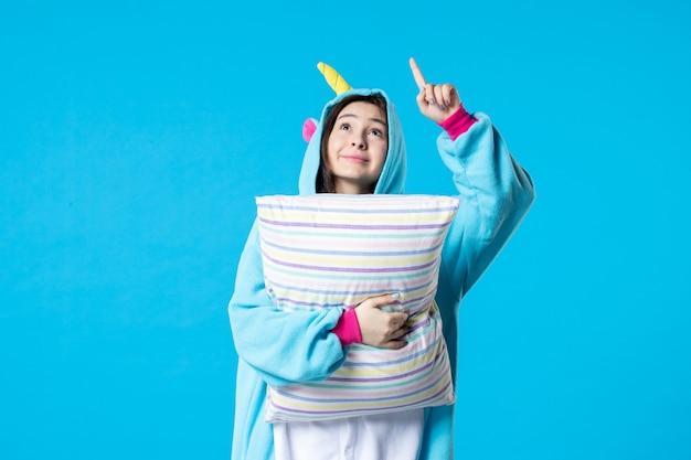 Vooraanzicht jonge vrouw in kigurumi voor pyjama party holding kussen op blauwe achtergrond cartoon spel droom slaap vrienden plezier kleur anime laat bed