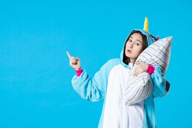 Vooraanzicht jonge vrouw in kigurumi voor pyjama party knuffelen kussen op blauwe achtergrond cartoon droom anime slaap laat bed spel nacht plezier kleur