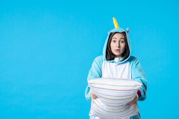 Vooraanzicht jonge vrouw in kigurumi voor pyjama party knuffelen kussen op blauwe achtergrond cartoon droom anime slaap laat plezier bed spel nacht kleur