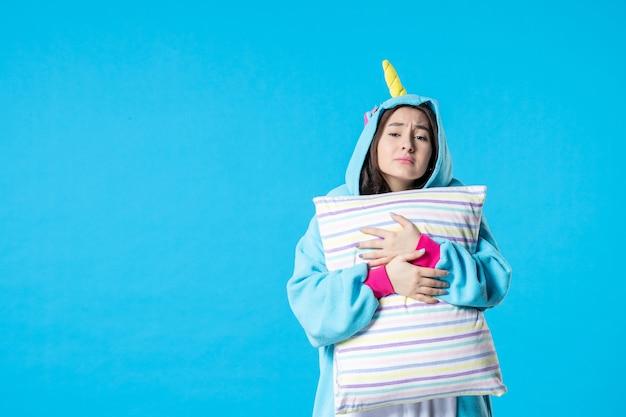 Vooraanzicht jonge vrouw in kigurumi voor pyjama party knuffelen kussen op blauwe achtergrond cartoon droom anime slaap laat plezier nacht vrienden bed spel kleur