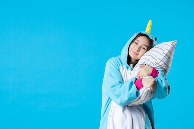 Vooraanzicht jonge vrouw in kigurumi voor pyjama party knuffelen kussen op blauwe achtergrond cartoon droom anime slaap laat plezier vrienden bed spel kleur
