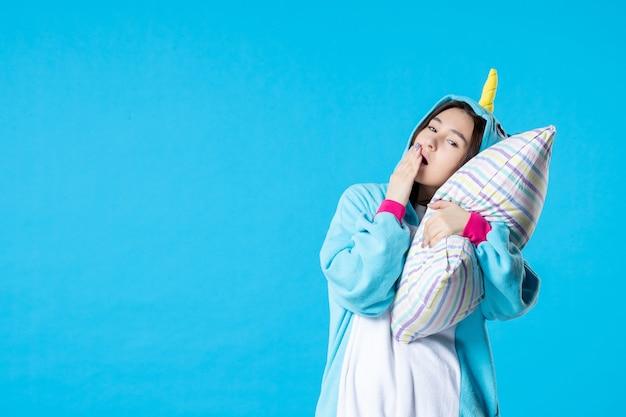 Vooraanzicht jonge vrouw in kigurumi voor pyjama party knuffelen kussen op blauwe achtergrond cartoon droom anime slaap laat plezier vrienden bed spel nacht kleur geeuw