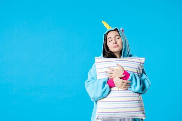Vooraanzicht jonge vrouw in kigurumi voor pyjama party knuffelen kussen op blauwe achtergrond cartoon droom anime slaap laat plezier vrienden bed spel nacht kleur