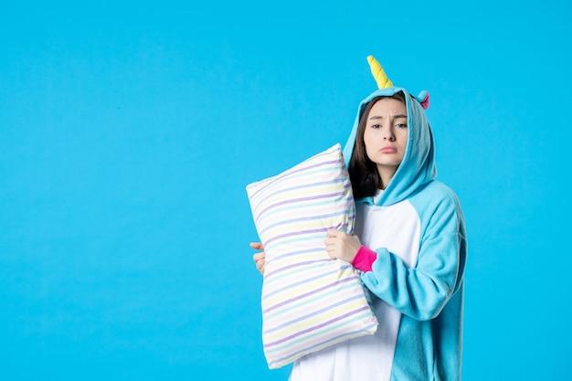 Vooraanzicht jonge vrouw in kigurumi voor pyjama party knuffelen kussen op blauwe achtergrond cartoon droom anime slaap laat plezier vrienden bed spel nacht kleuren