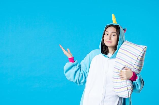 Vooraanzicht jonge vrouw in kigurumi voor pyjama party knuffelen kussen op blauwe achtergrond cartoon droom anime slaap laat vrienden bed spel nacht kleur