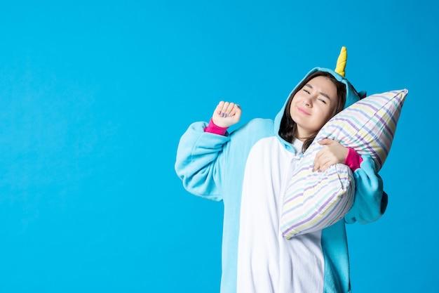 Vooraanzicht jonge vrouw in kigurumi voor pyjama party knuffelen kussen op blauwe achtergrond cartoon droom anime slaap laat vrienden bed spel nacht plezier kleur