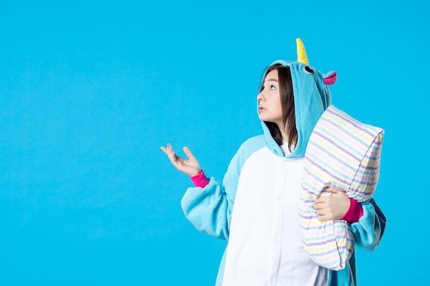 Vooraanzicht jonge vrouw in kigurumi voor pyjama party knuffelen kussen op blauwe achtergrond cartoon droom anime slaap laat vrienden bed spel nacht plezier kleuren